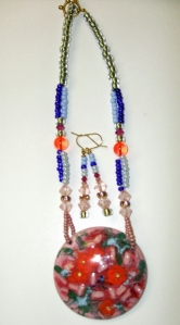 Red & pink stone with clear, blue, white beads. Necklace and earring set #