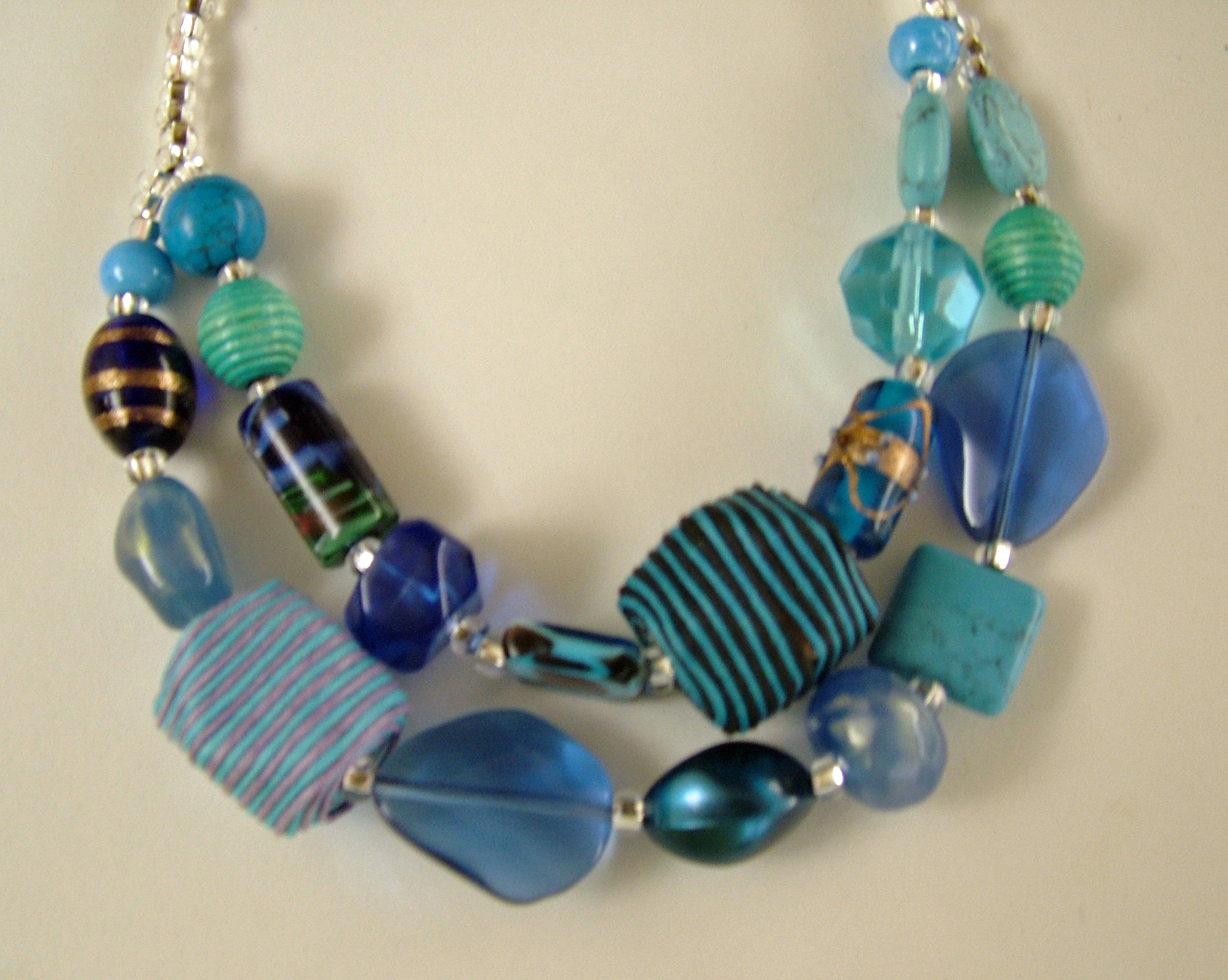 Two strand necklace with a collection of large blue glass